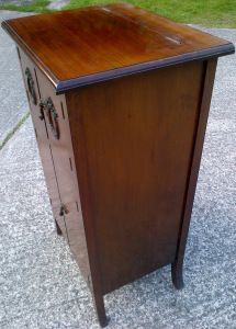 the left hand side of the gramophone cabinet