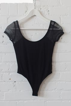 Simple black short sleeve bodysuit with mesh sleeves. Flattering round neck and round open back. Snap button crotch for easy on and off closure. Made with lightweight and stretchy jersey knit material.  85% Rayon 10% Polyester 5% Spandex Made in USA