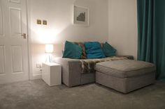 Lounge with newly fitted grey carpet. Teal accent colour.