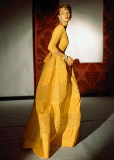 Jean Patchett 1948 Jean is wearing a lemon yellow evening dress with 3/4 length sleeves in stiff taffeta and lace from the Empire line, made to order at Henri Bendel.