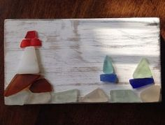Wooden art panel with lighthouse on cliff showing sail boats in; made of genuine sea glass collected from the San Francisco Bay Area, naturally