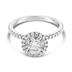Ecali Presents: A 1ct round brilliant cut diamond takes centre stage in a classic white gold engagement ring, accented by a diamond band and delicate claw set halo.