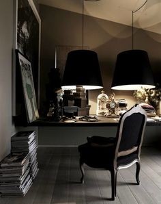 I like absolutely everything: the chair, the pile of magazines, the leaning frame, the black lamp shades - and especially the dominating black.