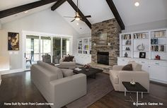Great room with a fireplace and wooden ceiling beams! New photos of The Carinthia house plan 1180 built by North Point Custom Builders! #WeDesignDreams #DonGardnerArchitects