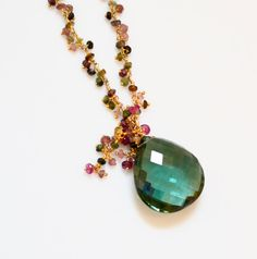 This heart shaped, emerald green quartz gemstone is stunning. It is huge (29mm x 26 mm x 11mm) and is faceted for incredible sparkle. Clustered at the top of this gorgeous focal are pink AAA tourmaline beads and tourmaline vermeil dangling chain.  The hand-crafted, 2mm multi color tourmaline, vermeil dangling chain is attached to an etched 14kgf chain The lobster clasp and extension chain are 14k gold filled. A one of a kind statement necklace Length 17 inches with a 2 inch extension chain…