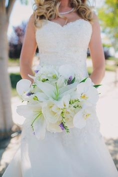 A white bouquet of roses, orchids, and lilies | @lindsgomes | Brides.com
