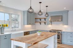 Farmhouse kitchen with light blue cabinets, single basin farmhouse sink, viking range and wood counter island painted white
