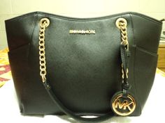 [C-MK-0011] Cartera color negro; 2 bolsas laterales externas; 1 bolsa interna con zipper; 2 compartimientos internos para celulares u otros accesorios.