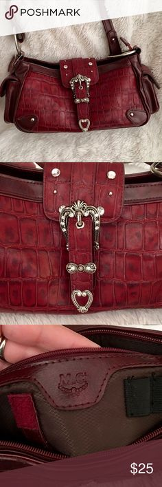 NWOT M.C. Burgundy silver & rhinestone purse NWOT burgundy, silver & rhinestone purse- side pockets. Middle compartment zips completely with many compartments plus one on outside back. M.C. Bags Shoulder Bags