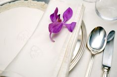 Bright purple floral wedding table setting, photo by Joanne Dunn
