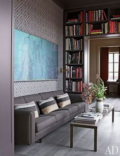 Ed Filipowski and Mark Lee's traditional prewar penthouse became an urbane showpiece in the hands of architect Mark Janson; Filipowski and Lee, both fashion executives, decorated the place themselves. The library's varying gray palette includes dark shelves, a slate-color Hans J. Wegner sofa, and a vibrant David Hicks wall covering from Lee Sofa | archdigest.com