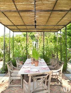 The outdoor dining area's pergola features a steel frame topped with bamboo matting | archdigest.com