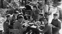 Suomalaiset sotilaat ruokailevat lottien kenttäkeittiössä Kivennapa, Karjalan kannaksella. SA-kuva.
