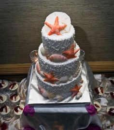 Wedding Cakes: Beach wedding cake with orange and pink starfish and seashells