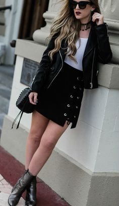 Black and white edgy spring transition outfit styled with black leather jacket, lace up skirt, metallic booties, and fringe choker