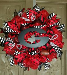 "This is a hand crafted 24"" University of Georgia deco mesh wreath. The wreath is made of red, black and white mesh and accented with red, white and black ribbons and a black wooden Georgia G letter. A"