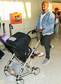 Kanye West cracked a smile as he pushed baby girl North West through the JFK International Airport with wife Kim Kardashian on Sunday, Sept. 6.
