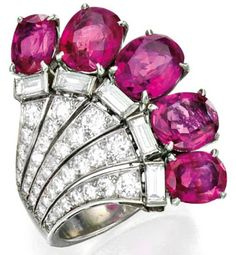 Art Deco cocktail ring, circa 1935. This ring is of fan-shaped motif and is set with five cushion and oval-shaped pink sapphires weighing approximately 7.20 carats. The ring is further accented with numerous old European, single-cut and baguette diamonds weighing approximately 1.50 carats. Via Diamonds in the Library.