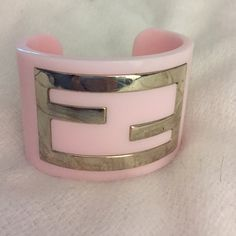Fendi authentic logo cuff bracelet Authentic Fendi cuff bracelet with gold tone logo embellishment at front. embellishment has a few scuffs but not noticeable. FENDI Jewelry Bracelets