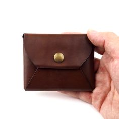 A minimalist wallet or simple coin purse, handmade by a community of skilled artisans, using vegetable-tanned leather. This tanning process uses materials such as bark and leaves instead of harmful chemicals like chromium. We also only use plant based dyes to ensure both our people and the environment are happy!