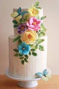 Esperando la primavera... Tarta de estilo rústico con una base imitando a madera clara y unas flores de colores vibrantes.                  ...