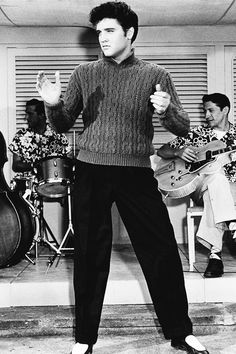 """Elvis - classic image from """"Jailhouse Rock"""" - iconic look in 'that' sweater / singing """"You're So Square, Baby I Don't Care"""" - Scotty Moore on guitar & DJ Fontana on d rums in the background.  On the recording, Elvis is actually playing a Fender bass instead of Bill Black.  In the movie, it is a visual 'goof' because Bill is strumming and slapping the stand up base with which he was most familiar up to that point."""