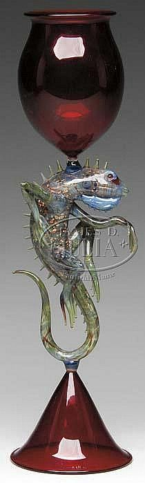 """IGUANA CHALICE. Exceptional art glass chalice has ruby red foot and cup which are connected by a wonderfully detailed glass Iguana with blue, green and brown speckled body, sharp spines extending down the back from head to tail as well as long legs with long slender  toes. 15 1/4"""" Tall"""