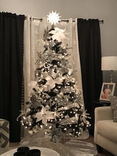 Black Christmas tree with silver and white decorations. Decorated by Donna Munoz