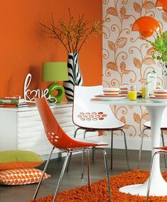 You can't' help but to be drawn to this modern & colorful dining are with that fabulous wallpaper, the mixture of green and orange and I love the addition of the black and white vase.
