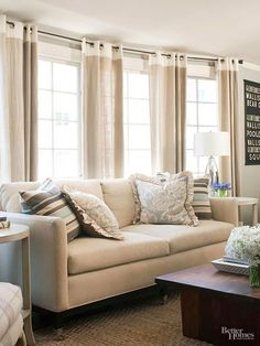 A sofa finds the perfect home in a bay of windows. Drapery panels hang from grommets on a custom curved-iron rod. Panels soften the expanse and call attention to individual windows. Adding interest, yet maintaining the neutral scheme, the top band of the window treatments is white, and the lower portion is a loose linen weave.