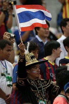 A Thailand supporter waves the national flag during the international friendly match between Thailand XI and FC Barcelona at Rajamangala Stadium on August 7, 2013 in Bangkok, Thailand.