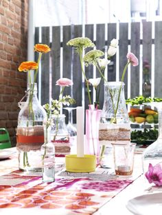 DIY wedding decor - Wrap fabric and ribbons around clear glass vases from IKEA for a unique, inexpensive, and easy tabletop display.