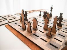 Portable chess set with flat, laser cut pieces that slot into the chess board during play. When not in use, the set flattens into 4 wooden tablets that stack