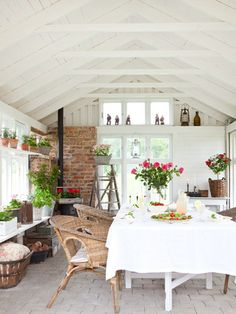 Sunroom porch, white ceiling, beams, fireplace, wicker, white, greenery, light