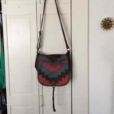 southwestern crossbody bag Brown crossbody bag with a long adjustable strap. The pattern on front strikes me as southwestern, and is brown, blue, and a color that's kind of in between rust and pink. Braided rope detail on the front. Bags Crossbody Bags