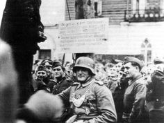 "German field gendarme (military policeman, with helmet) and crowd of German soldiers next to the gallows where a suspected partisan has just been hanged. The board nailed to the gallows reads: """"Such is the fate that befalls every partisan and [communist] Commissar and those who oppose the German army."""