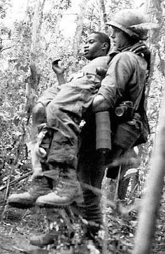 A US soldier carries a wounded comrade to safety during Operation Attleboro, near Tay Ninh, Republic of Vietnam, November 4, 1966.