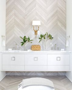 """A chevron-patterned wall and floor employs gray """"stained"""" wood tile to create serenity in this shared bath."""