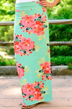 This stylish maxi skirt features a bold floral print on a background of mint