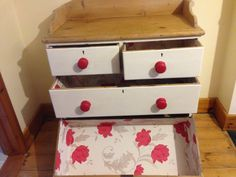 cream chest of drawers with red flower lining and red knobs