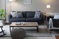 mur gris clair et canapé gris foncé, coussins graphiques, table basse bois clair