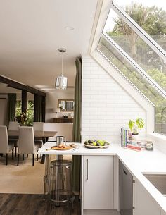 This white kitchen maximises the views of the harbour and bush. The result is a light, airy space which feels restful and links effortlessly to the treetop views. Photography by: Helen Bankers. Mid Century House, House, Home, Family Living, Kitchen Decor, Wood Look Tile, New Kitchen, Kitchen Design, Wood Burning Stove