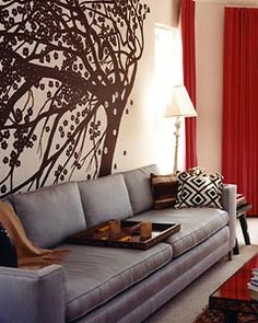 Beautiful...just don't think I could have that much going on in the living room.     Dramatically Bold Living Room    M. Design Interiors    The blooming tree wall decal adds an ever-present feeling of motion to the living room. The red curtains in the corner add drama to the room.