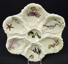 Antique Haviland & Co. Sea Life Oyster Plate: Produced in France by Haviland & Co. Limoges between 1876 & 1879. It has a double mark from the factory indicating this period. It was made especially for the retailer Brodhead & Hamlin of Syracuse, NY. There is space for 6 shells & it has a center salt dip. Each section has transfer decorations of sea life that are hand colored. There are different types of sea weed, shells, a star fish, etc.