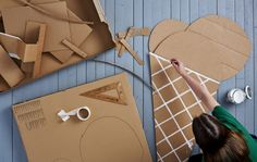 An image from above of a woman painting cardboard shaped like a giant ice cream cone.