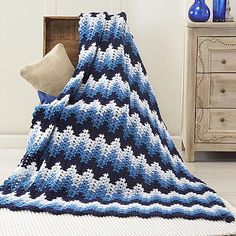Snuggle up with elongated ripples crocheted in four shades of blue contrasted with white for warm and cozy winter décor.