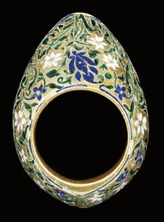 A GREEN AND BLUE ENAMELLED SILVER GILT ARCHERS RING, LUCKNOW, PROBABLY LATE 18TH CENTURY  Of typical form, decorated with blue and white flowers on long leafy green stems, a thin band of blue to edges, further scrolling green vine to underside - 1 3/4in (4.3cm) long