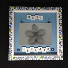 """White wooden scrabble letters saying """"Best Stepmum"""" with hand painted wooden flowers. Two wooden flower pegs to hold a inch photo. Photo for demonstration use only. The frames are white,Wooden with a flower trim. Scrabble Letters, Wooden Flowers, Mothers Day Presents, Gift Guide, Hand Painted, Frame, Picture Frame, Frames, Wood Flowers"""