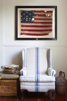 """We found the old centennial American flag wadded up on a shelf at an estate sale and brought it home for $3. I couldn't live without the grain sack chair. Andrea, who owns our amazing local home goods store (Southern Antiques), found the tired old wingback chair and had it recovered in a nubby, authentic French grain sack. It's my favorite piece of furniture."""""""