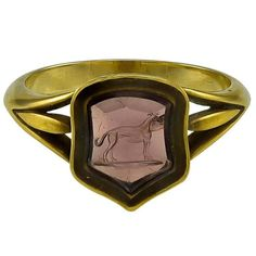 A petite Georgian Almandine Garnet Intaglio Ring. The slightly shield shaped red/mauve Garnet is engraved with the image of a Greyhound standing on a ground line. This is part of an Heraldic Crest and would have been used for sealing minor documents and personal letters. The Gem is set in an unmarked 18k ring mount with slim trefoil shoulders, c 1820